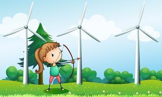 En tjej med en bågskytt nära väderkvarnarna