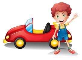 En ung pojke framför en röd bil