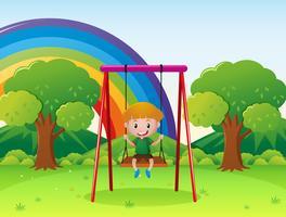 Liten pojke spelar på gungan i parken