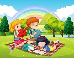 Barn läser böcker i parken