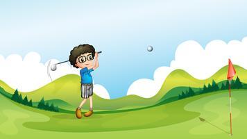 En pojke som spelar golf på fältet