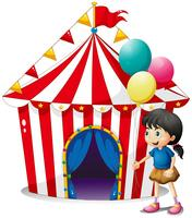 En tjej med ballonger framför cirkustältet