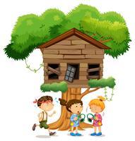 Kinder spielen vor dem Baumhaus