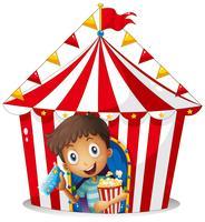 Ein Junge mit einem Ticket und einem Popcorn in der Nähe des Zeltes