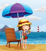 Eine junge Frau, die eine Eiscreme am Strand isst