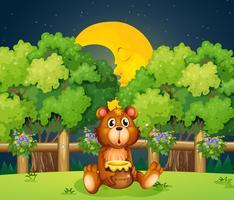 En björn vid skogen i mitten av natten