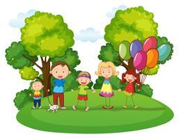 Familj med tre barn leker i parken