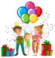 Familj på födelsedagsfest med ballonger och presenter