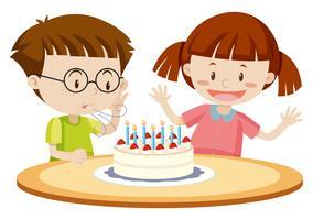 Barn blåser tårta på födelsedagen