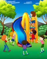 Många barn spelar glid i parken