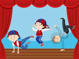 Tre barn dansar på scenen
