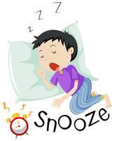 Pojke sover med väckarklocka snoozing