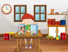 Junge und zwei Gläser mit Murmeln im Klassenzimmer