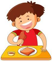 Pojke som äter kyckling på bordet