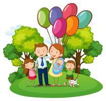 Familj med tre barn i parken