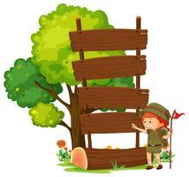 Campingpojke med tomt träskylt