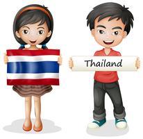Pojke och flicka med flagga i Thailand
