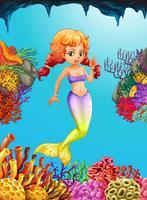 Söt sjöjungfrun som simmar under havet