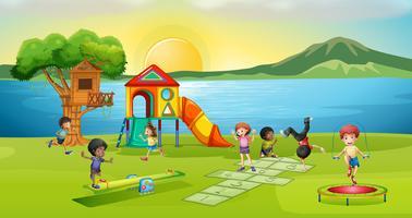 Kinder, die im Spielplatz bei Sonnenuntergang spielen