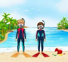 Två dykare i våtdräkt stående på stranden