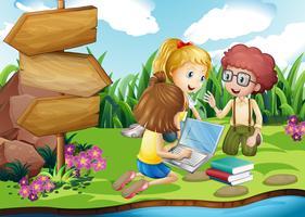 Barn arbetar på dator i parken