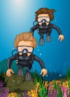 Två dykare dykning under havet