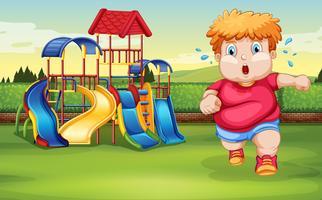 En fet pojke som kör på parken