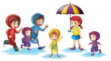 Barn som bär regnrockar under regnperioden