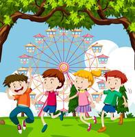 Lyckliga barn leker i park med pariserhjul i bakgrunden