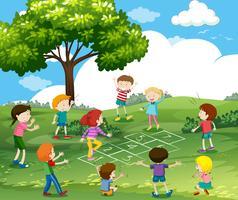 Lyckliga barn leker hopscotch i parken