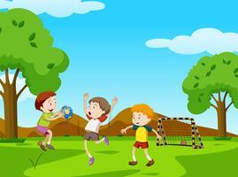 Tre pojkar spelar boll i parken vektor