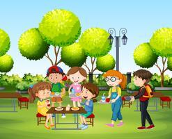 Människor äter i parken på dagtid vektor