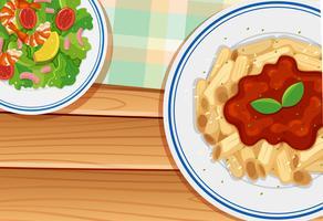 Teigwaren und Salat auf Holzbrett vektor