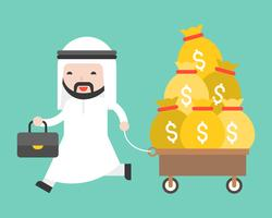 Glücklicher netter arabischer Geschäftsmann, der Wagen voll mit Geldbeutel zieht