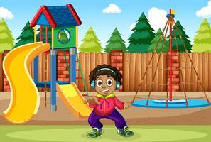 Ein Junge hört Musik auf dem Spielplatz vektor