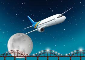 Flygplan som flyger över bron på natten