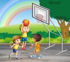 Drei Kinder, die am Gericht Basketball spielen