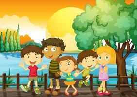 Barn på bron vid solnedgången