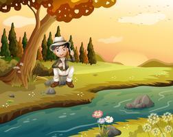 Ein Junge, der nahe dem Flussufer sitzt vektor
