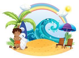 En pojke som står bredvid sin surfingbräda på stranden