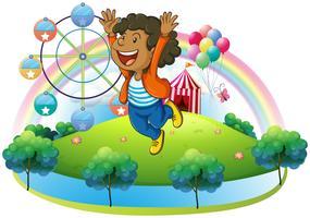 Ein glücklicher Junge auf dem Hügel mit einem Karneval vektor