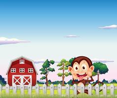 Ein Affe in der Nähe des roten Scheunenhauses