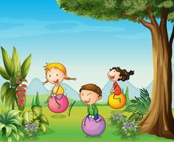 Tre barn har kul med en studsande boll vektor