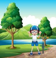 En ung pojke och hans leksakcykel står nära träd i flodbredden vektor