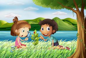 Barn nära floden med förstoringsglas