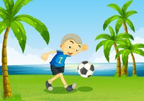 Ein junger Fußballspieler am Flussufer mit Palmen vektor