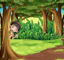 En ung tjej gömmer sig i skogen vektor