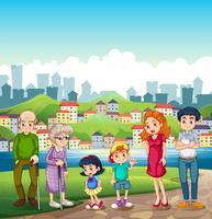 Eine große glückliche Familie, die am Flussufer gegenüber des Dorfes steht