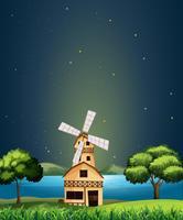 Ein hölzernes Scheunenhaus am Fluss mit einer Windmühle