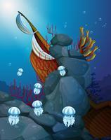 Maneter under havet med ett skadat skepp
